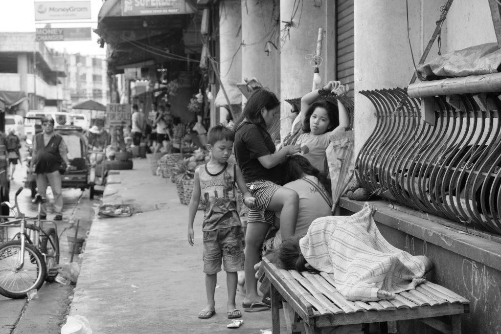 A PUBLIC LIVING ROOM. Children of ambulant vendors play, rest, sleep even on the side of a closed bank along Lopez Jaena Street near Margarita Avenue. |Photo by Lourdes Rae Antenor, text by Julius D. Mariveles