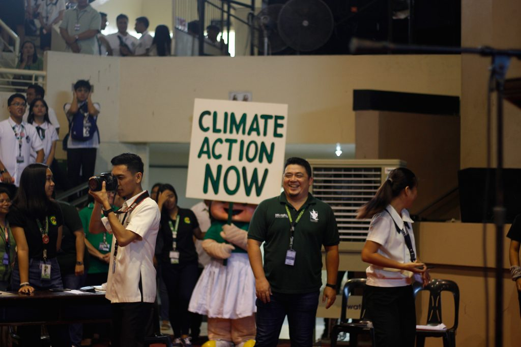 Balayan Director Andre Tagamolila, the event MC, joins the chant for climate action as the official mascot sends an important message to forum participants and audience.