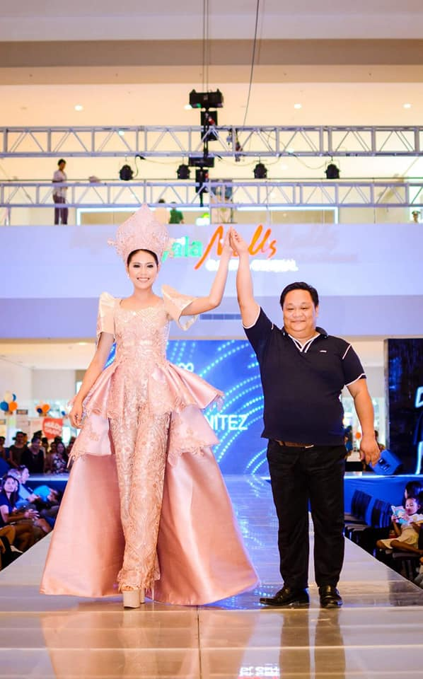 Edwin Benitez with one of his creations.  His gowns define pomp and pageantry. Photo taken with permission from the designer's Facebook page.