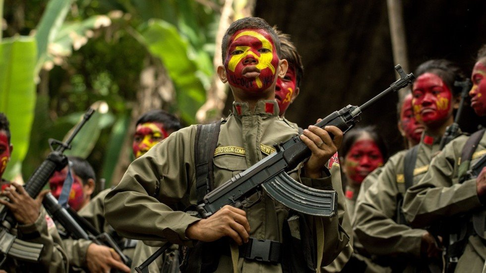 Red fighters of the New People's Army had their faces painted with the CPP flag in an unknown NPA base. | Photo from Philippine Revolutionary Web Central.