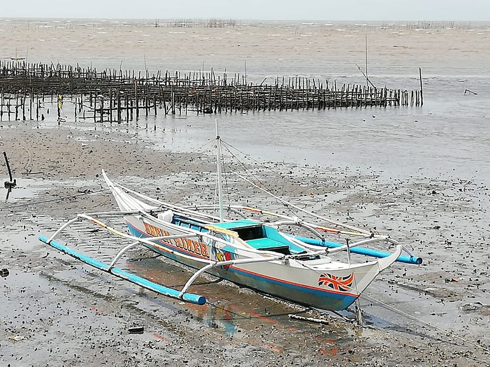 PAGASA downgrades storm warning signals in Negros Occidental but provincial disaster chief advises residents to stay alert. | Caption: a banca on the shore of a coastal village in Negros Occidental.