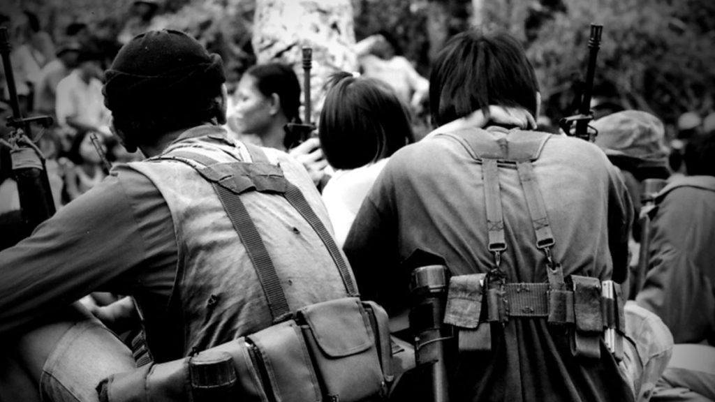 COMRADES IN ARMS. Two Red fighters of the CPP New People's Army with ammo watches a cultural presentation during celebrations for the founding of the Communist Party of the Philippines more than a decade ago in Negros island, Philippines. This was originally shot using colored film. | Photo by Julius D. Mariveles