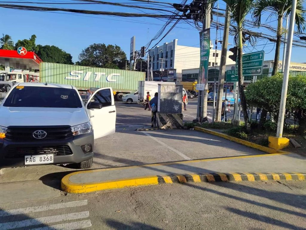 MURDER PAST HIGH NOON. The body of Police Officer 1 Eric Alcosaba lies on the roadside. He ran a few meters away from his parked vehicle in front of the McDonald's store along Burgos Avenue. | Photos courtesy of BCPO.